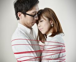 Couple hugging red thread is wound around